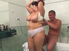 She sucks on his cock and lets him fill her mature pussy in the bathroom